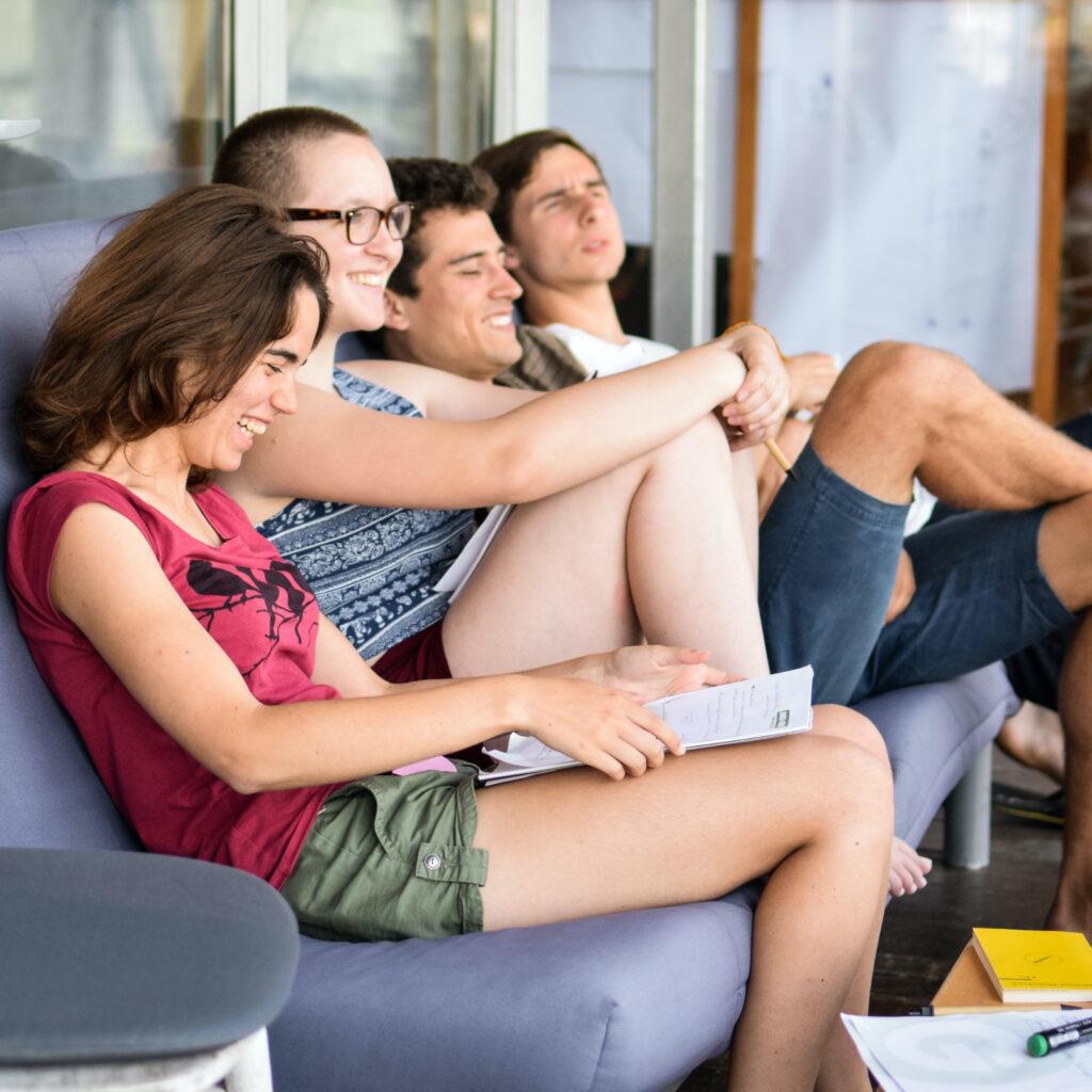 Junge Menschen lesen einen Text und lachen.