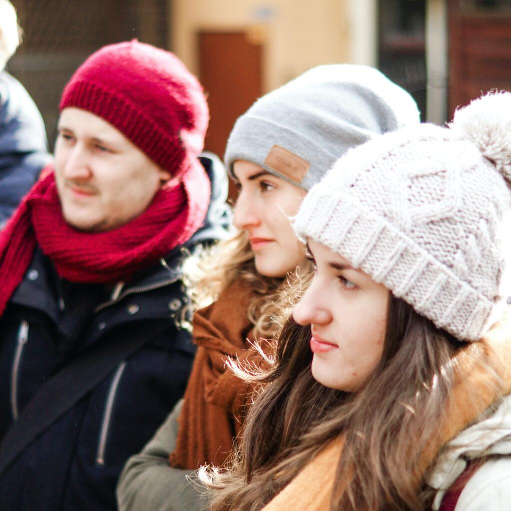 Vier junge Menschen hören interessiert zu.