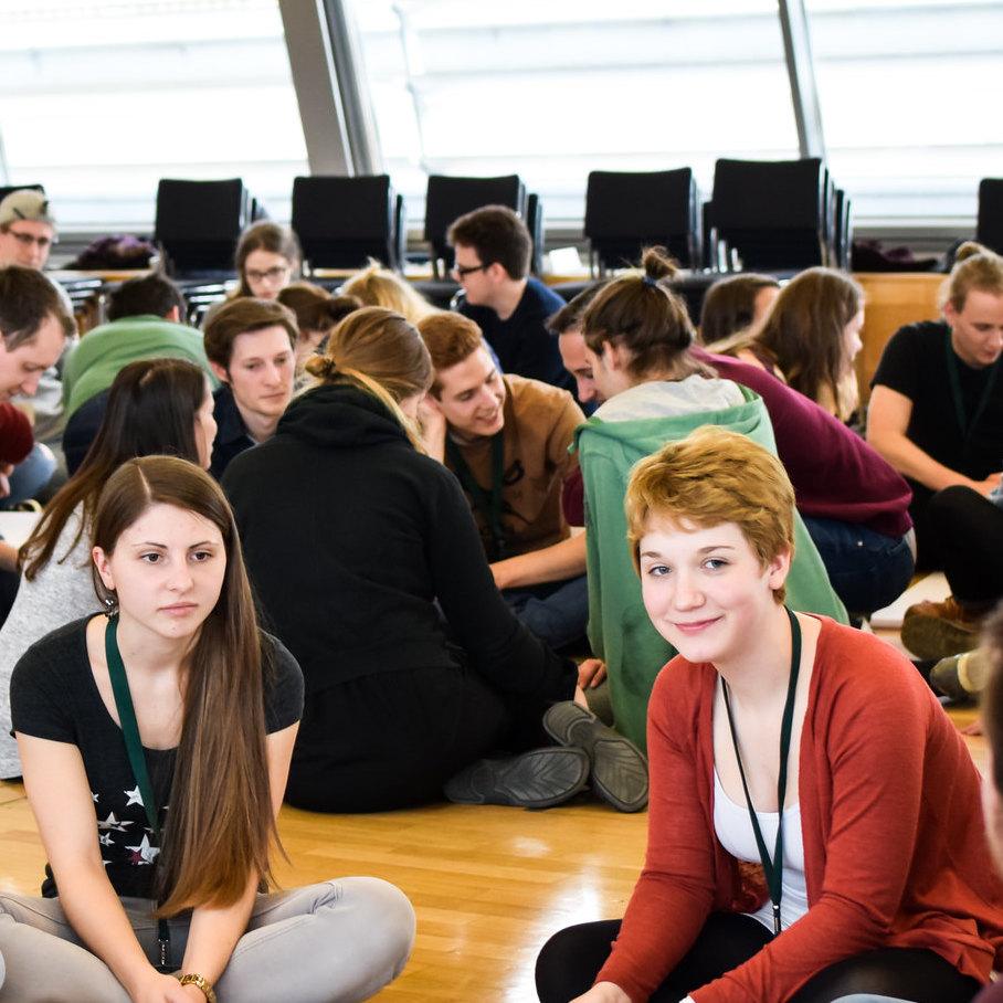 Junge Menschen sitzen in im Kreis und diskutieren.