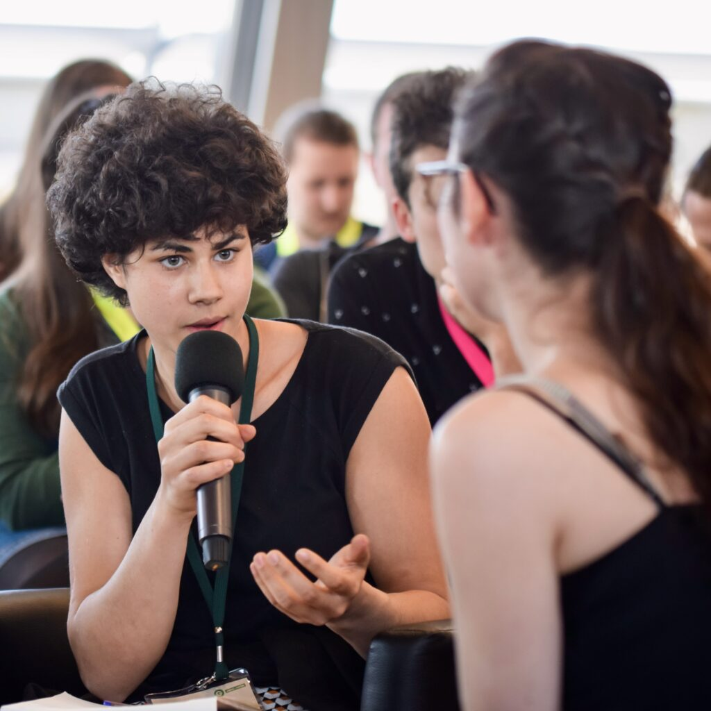 Eine junge Frau hält einen Redebeitrag.